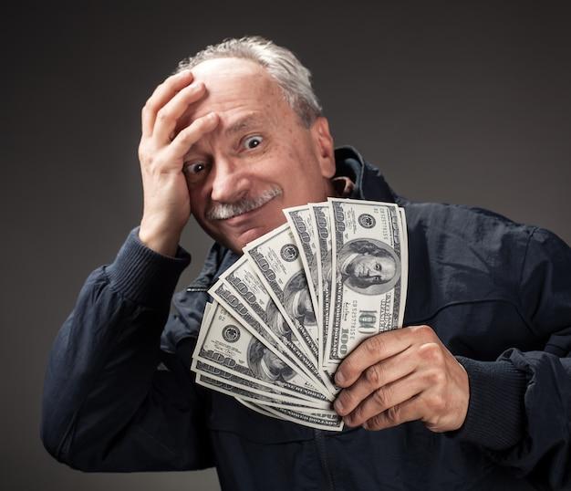 Старик держит группу долларовых купюр
