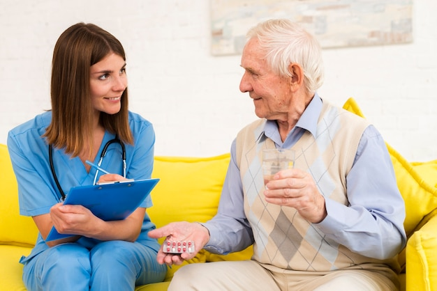 Old man holding his pills while talking to a nurse