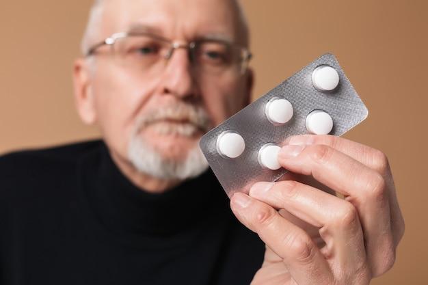 Старик, держащий таблетку с портретом таблетки