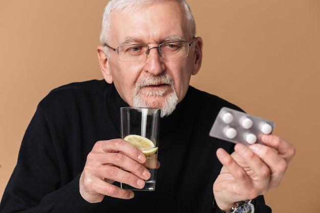 錠剤の肖像画とタブレットを保持している老人