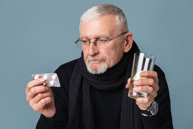 Old man holding tablet with pills portrait