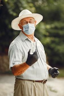 Старик в медицинской маске. мужчина в парке. тема коронавируса.