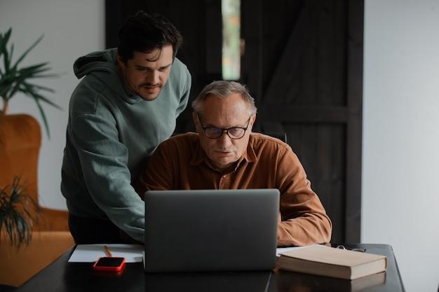 Старик в очках и его сын с помощью портативного компьютера дома.