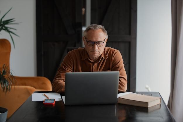 Старик в очках с помощью портативного компьютера дома.