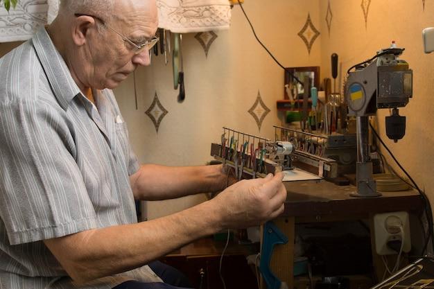 작은 갈색 플랫폼에서 전자 장치를 혁신하는 회색 폴로의 노인.
