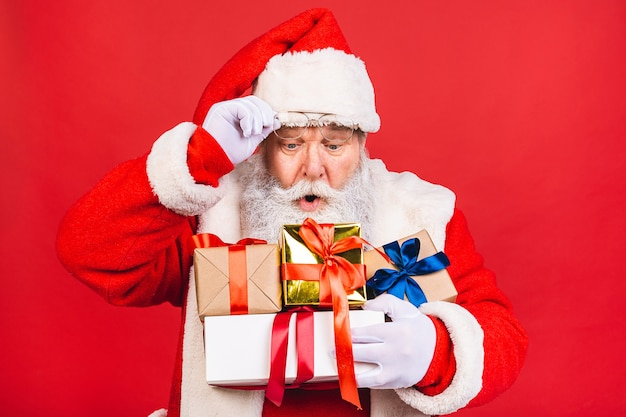 Старик в костюме санта-клауса держит кучу подарков на красном фоне