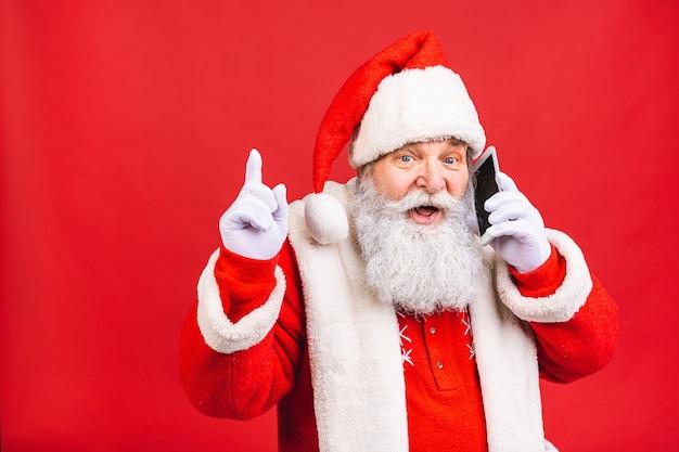Старик в костюме санта-клауса разговаривает по мобильному телефону на красном фоне