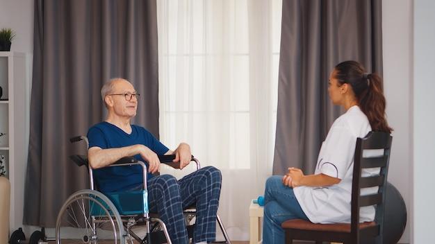 医者と話している車椅子の老人。ナーシングホーム支援、ヘルスケア、医療サービスの医療従事者を持つ障害者高齢者