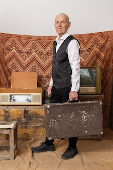Старик в белой рубашке держит старый классический багажный багаж, стоит среди старинных комнат со старым телевизором и радио