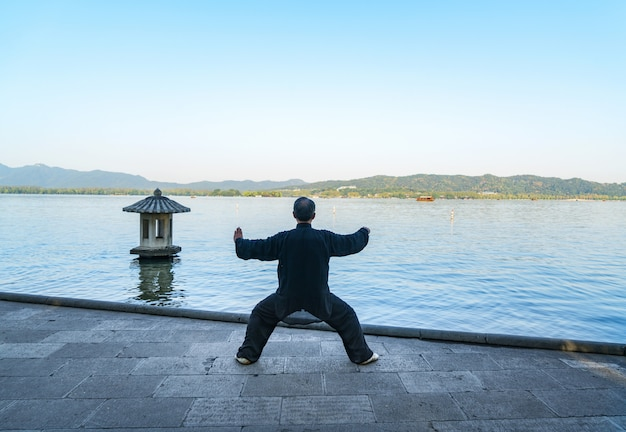 The old man is practicing taijiquan on the side of west lake, hangzhou, china.