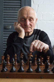 An old man is sitting in front of a chessboard