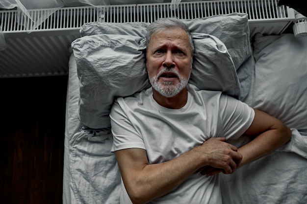 Old man is stressed out by getting sick on bed, holding hands on chest, he was diagnosed with high blood pressure and cancer.