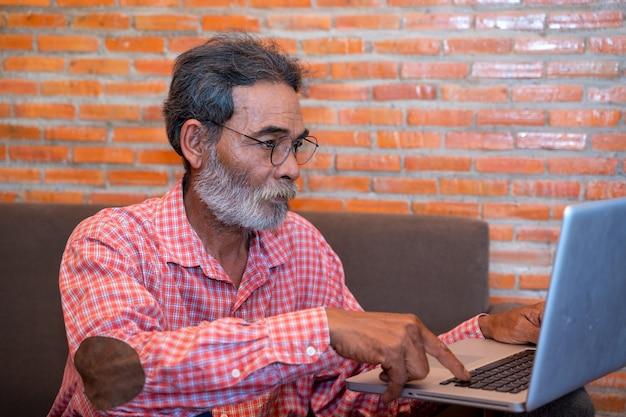 Старик учится пользоваться ноутбуком дома, старший человек пользуется компьютером за работой из дома