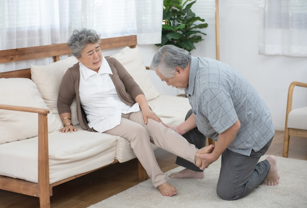Old man look after elder woman after hurt on leg