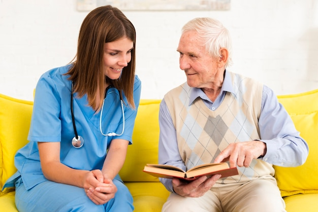 Old man looking on a book with a nurse