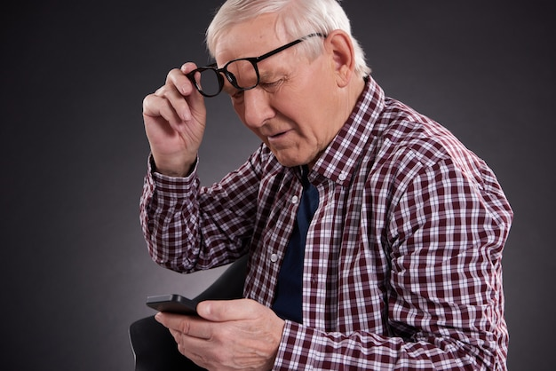 Old man looks into phone, lifting his glasses