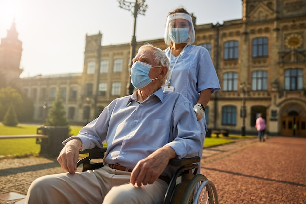 Old man in mask while sitting in wheelchair in yard