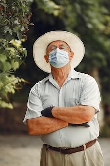 Uomo anziano in una mascherina medica. l'uomo nel parco. tema coronavirus.