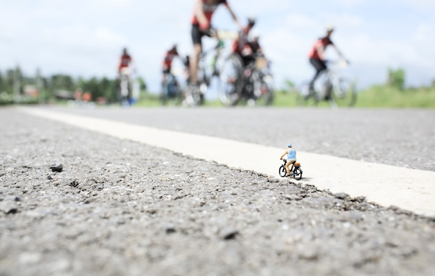 An old man  miniature on cycle ride in country road with a group of bicycle race background