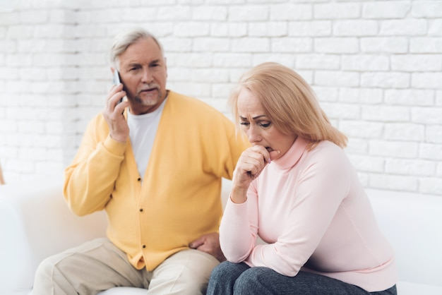 Old man near upset old woman talking on smartphone