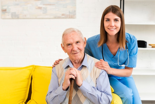 Old man and nurse sitting on yellow sofa while looking at the camera