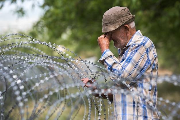 점령 된 tskhinvali 지역이있는 분리선에있는 철조망 근처의 지역 스탠드에있는 노인