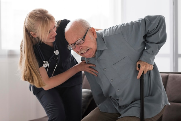 Old man in pain helped by nurse