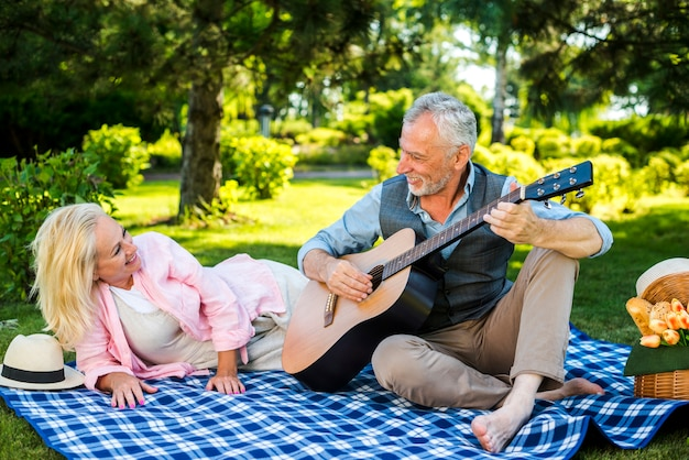 Old man playing guitar for his woman
