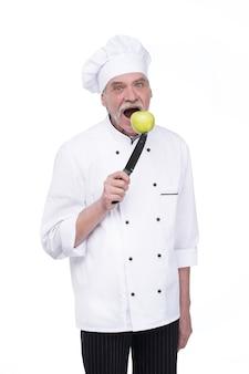 Старик, профессиональный повар в белой форме держит металлический нож с зеленым яблоком, стоя на белой стене