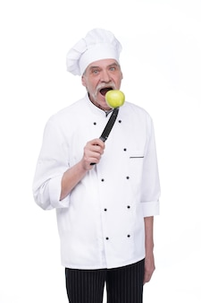 Old man, professional chef in white uniform holding metal knife with green apple while staying on white wall