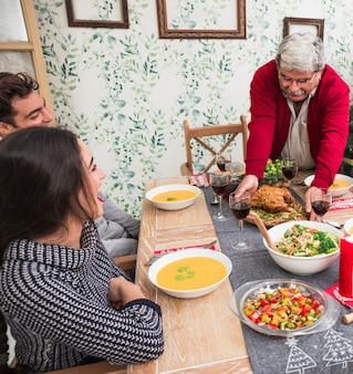 Old man putting roasted chicken on festive table