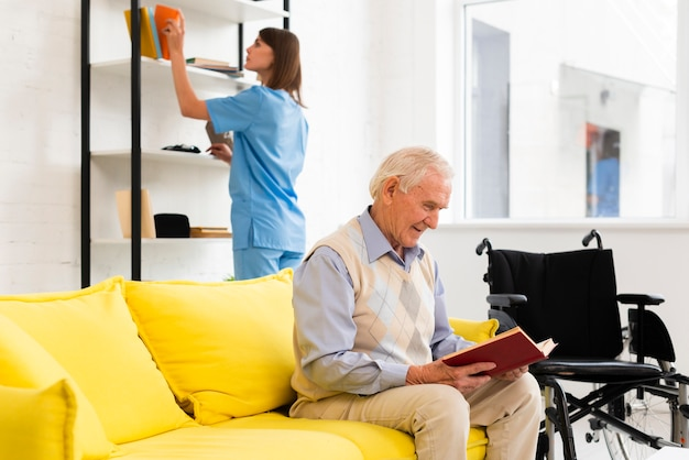 Old man reading a book while sitting on yellow sofa