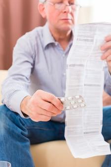 Старик читает листок-вкладыш с лекарствами дома в очках