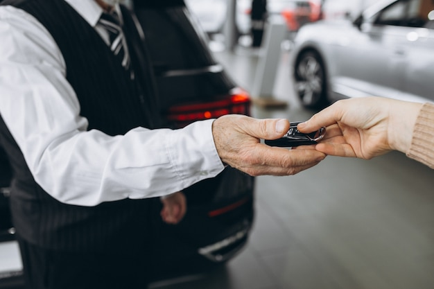 Old man receiving keys from car in a car showroom
