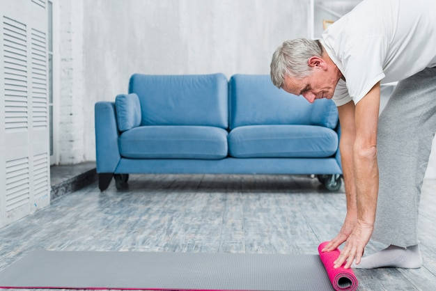 Old man rolling yoga mat on floor