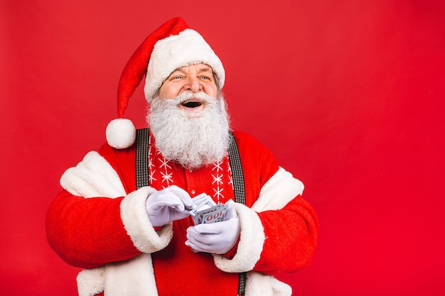 Old man in santa claus costume counting money isolated on red background