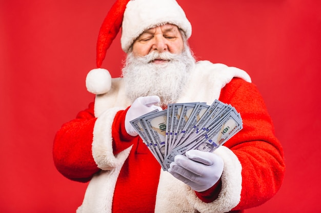 Old man in santa claus costume holding money isolated on red background