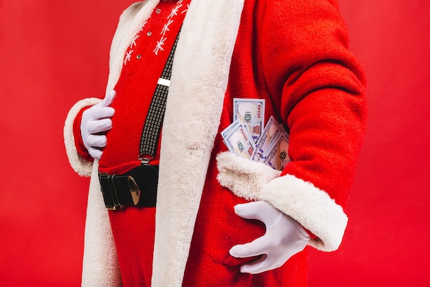 Old man in santa claus costume holding money in a pocket isolated on red background
