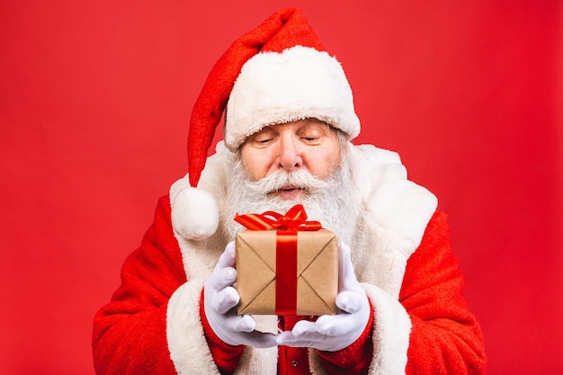 Old man in santa claus costume holding a present isolated on red background