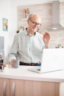 コーヒーを飲みながらキッチンでノートを使用して家族とのビデオ通話中に挨拶している老人。