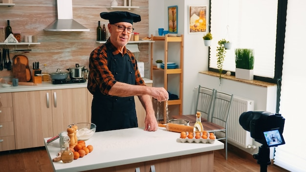 Старик снимает кулинарное видео с помощью камеры на штативе на кухне. блогер на пенсии, повар, влиятельный человек, используя интернет-технологии, общается, ведет блог в социальных сетях с помощью цифрового оборудования.