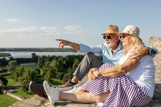 Old man showing woman a  view