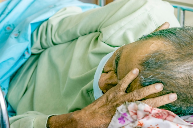 Old man sick on the bed  in a hospital.