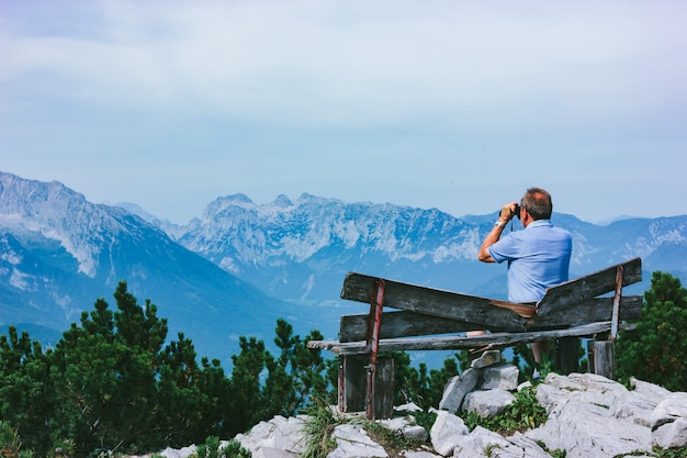 An old man sits on a wooden bench and looks at the alpine mountains through binoculars.