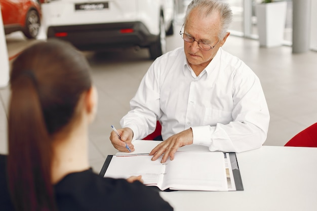 Old man sitting in a car salon and talking with manager