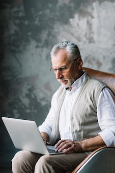 An old man sitting on chair typing on laptop