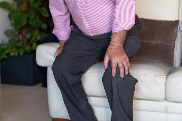 Старик сидит на диване и чувствует боль в колене и с