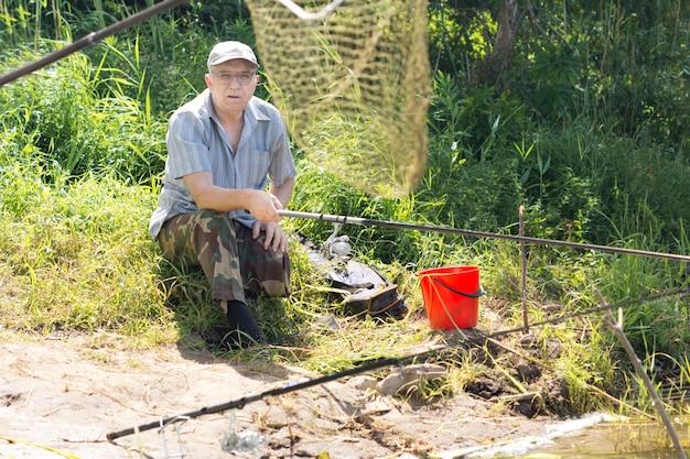 Old man sitting on riverbank fishing at daytime