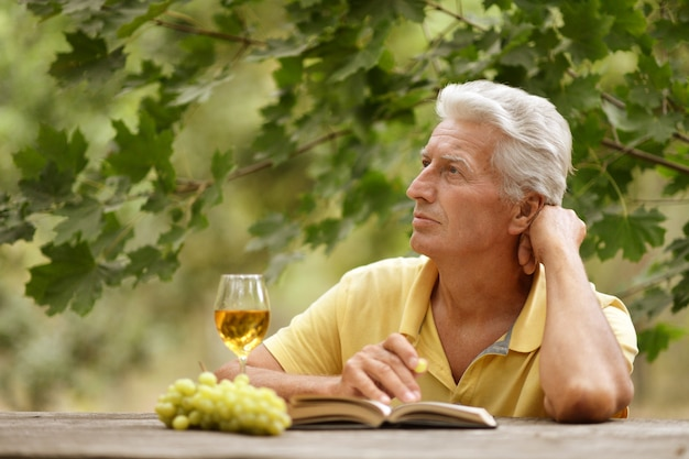 Old man sitting at a table, drinking wine and reading a book