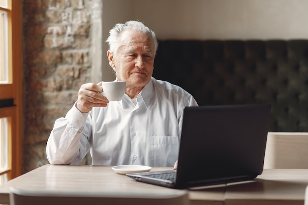 Old man sitting at the table and working with a laptop